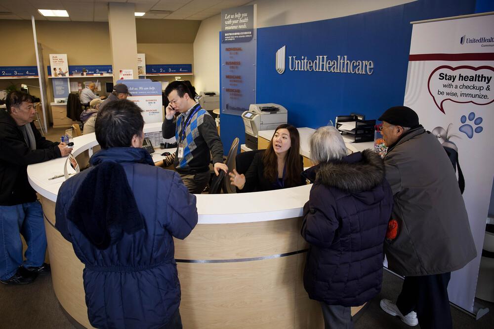 Клиенты получают информацию на стойке регистрации в магазине UnitedHealthcare в районе Квинс в Нью-Йорке, США, в понедельник, 14 января 2013 г. Эксперимент по продаже медицинских страховок потребителям в розничных магазинах, проводимый UnitedHealth Group Inc., крупнейшей в США Медицинское страхование призвано помочь компании конкурировать в ожидании радикальных изменений в соответствии с новым законом о здравоохранении. Фотограф: Майкл Нэгл / Bloomberg (Getty Images)