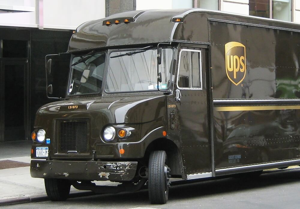 Немного потрепанный грузовик темно-коричневого цвета, компании UPS.